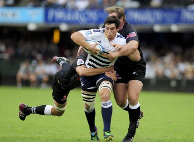 Keegan Daniel of the Sharks and team mate Jannie du Plessis tackle Francois Louw.