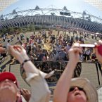 Members of the public take pictures of the Olympic Stadium reflected in a giant mirror. (Julien Behal/PA Wire)