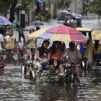 Residents negotiate a flooded street at Obando town, Bulacan province, north of Manila today. (AP Photo/Aaron Favila/PA)