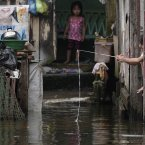 A Filipino girl plays with a mock fishing rod outside their flooded home at Valenzuela city, north of Manila today. (AP Photo/Aaron Favila/PA)
