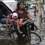 A young girl rides on a bicycle along a flooded street in Valenzuela city. (AP Photo/Aaron Favila/PA)