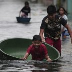 A Filipino boy plays along a flooded street in Obando town, Bulacan province, north of Manila today. (AP Photo/Aaron Favila/PA)