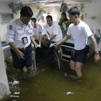 Security guards and staff push a patient on a wheelchair through a flooded emergency room in Valenzuela city, north of Manila. (AP Photo/Aaron Favila/PA)