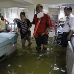 A man assists an elderly woman as they wade through a flooded emergency room at a hospital in Valenzuela city, north of Manila, today. (AP Photo/Aaron Favila/PA)