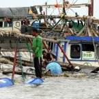 Fishermen gather empty plastic container from their half-submerge fishing boat following high tide and the storm in Navotas City north of Manila. (AP Photo/Pat Roque/PA)