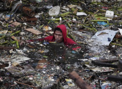 A Manila resident swims in polluted water as he attempts to salvage items from his destroyed home.