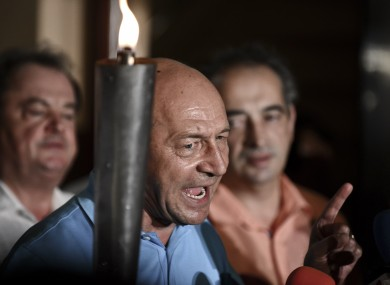 Suspended Romanian President Traian Basescu holds a torch while speaking at the end of the referendum on Romania's president impeachment day