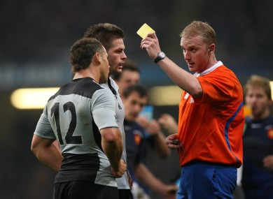 Referee Wayne Barnes gives Luke McAlister a yellow card in 2007.