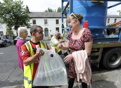 Local resident Rosemary McGinn collects water from a city council tanker on Castle Avenue yesterday.