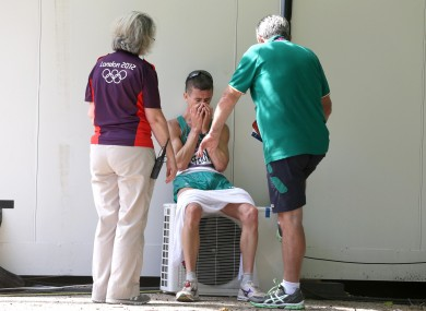 Rob Heffernan is consoled by an Olympic volunteer and Irish athletic team manager Patsy McGonagle after finishing 4th.