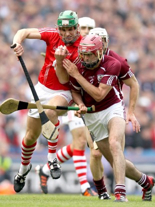 Cork's Eoin Cadogan and James Regan of Galway battle in yesterday's game.