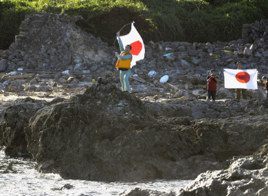 Japanese activists hold their national flag on Uotsuri island, one of the islands which is also claimed by China and Taiwan.