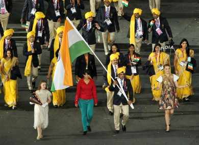 Madhura Nagendra, pictured in red, walks alongside India's Sushil Kumar as he carries the flag the athletes' parade.