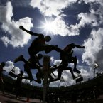 Athletes clear a barrier in a men's 3000-meter steeplechase heat during the athletics in the Olympic Stadium at the 2012 Summer Olympics, London, Friday, Aug. 3, 2012. (AP Photo/David J. Phillip)