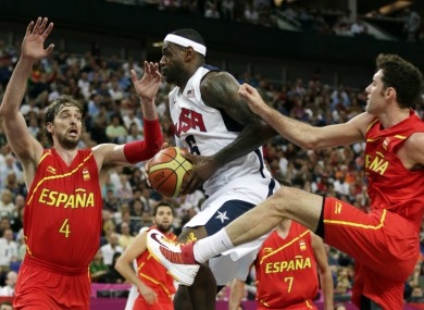 LeBron James drives between Spain's Pau Gasol and Rudy Fernandez.