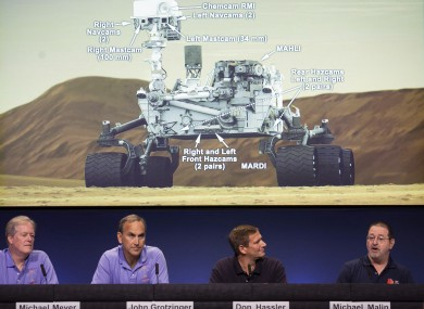 Scientists comment on the seven cameras aboard the Curiosity Mars Rover, background, during a media briefing of the Mars Science Laboratory