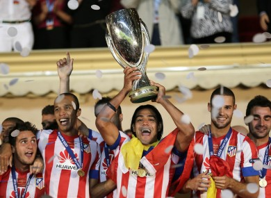 Atletico Madrid forward Falcao, of Colombia, holds the UEFA Super Cup with his teammates after defeating Chelsea.