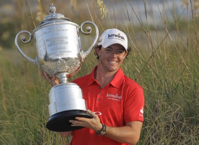 Rory McIlroy of Northern Ireland poses for photographers with the championship trophy after the final round of the PGA Championship golf tournament.