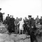 Princess Grace of Monaco uses a black-throne stick and wears flag heeled shoes, as she makes her way under escort of the Rev. Father to Cummins, left, and an unidentified man, during pilgrimage to the shrine of St Patrick at Croagh Patrick, Westport in 1961. (AP Photo)