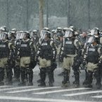 Police officers stand in a downpour as they watch demonstrators marching through the streets of Tampa, Florida, to protest against the Republican National Convention. (Chris O'Meara/AP/Press Association Images)