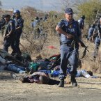 Police surround the bodies of striking miners after opening fire on a crowd  at the Lonmin Platinum Mine near Rustenburg, South Africa. An unknown number of people have been killed and injured when police moved in on workers who gathered on a rocky outcrop  near the Lonmin late afternoon, firing unknown ammunition.  (AP Photo)