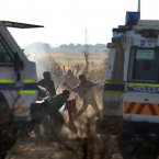 Striking mineworkers throw stones as police open fire on striking miners at the Lonmin Platinum Mine near Rustenburg, South Africa. South African police opened fire on a crowd of striking workers at a platinum mine, leaving an unknown number of people injured and possibly dead. Motionless bodies lay on the ground in pools of blood. (AP Photo)