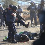 Police surround the bodies of striking miners after opening fire on a crowd  at the Lonmin Platinum Mine near Rustenburg, South Africa. An unknown number of people have been killed and injured. Police moved in on workers who gathered on a rocky outcropping near the Lonmin late afternoon, firing unknown ammunition.  (AP Photo) SOUTH AFRICA OUT