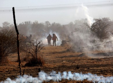 Striking Lonmin mineworkers amidst tear gas as police opened fire.