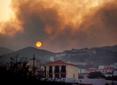 Smoke billows across houses as a wildfire burns near Chipude Village, La Gomera, Spain
