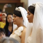 Huang Mei-yu, left, and her partner You Ya-ting arrive in the prayer hall to be married in the first same-sex Buddhist ceremonial wedding in Taoyuan, Taiwan, Saturday. (AP Photo/Wally Santana)