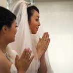 Huang Mei-yu, left, and her partner You Ya-ting pray before the first same-sex Buddhist ceremonial wedding in Taoyuan, Taiwan, Saturday. 