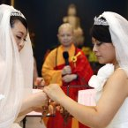 You Ya-ting, left, and her partner Huang Mei-yu exchange prayer beads as they are married by a nun in the first same-sex Buddhist ceremonial wedding in Taoyuan, Taiwan, Saturday. (AP Photo/Wally Santana)