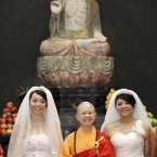You Ya-ting, left, and her partner Huang Mei-yu stand with Buddhist nun Shih Chao-hui in front of a statue of Buddha in the prayer hall after marrying in the first same-sex Buddhist ceremonial wedding in Taoyuan, Taiwan, Saturday. 