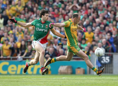 Colm McFadden of Donegal holds off Ger Cafferkey of Mayo.