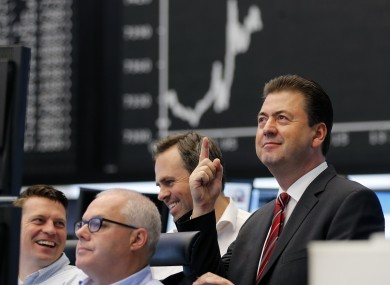 A trader smiles as news of the German constitutional court's ruling on a challenge to the ESM filters through in Frankfurt.