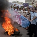 Pakistani traders burn a representation of a US flag next to burning tires during a rally in Islamabad, Pakistan today. (AP Photo/Anjum Naveed)