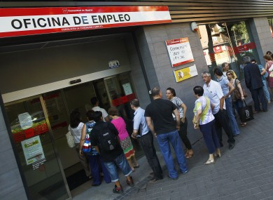 People queue outside an unemployment office in Madrid, Spain.