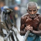 An elderly Sri Lankan laborer pushes a cart as it rains in Colombo, Sri Lanka. (AP Photo/Eranga Jayawardena)