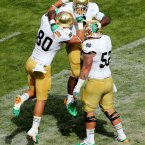 Notre Dame's running back Theo Riddick celebrates scoring the opening touchdown with Tyler Eifert and Braxston Cave.