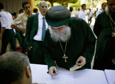 A Coptic clergyman registers for voting with election workers during the new Coptic Pope elections at the main Coptic cathedral in Cairo.