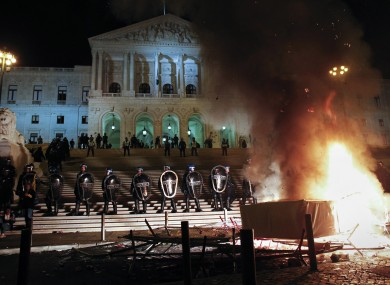 Riot policemen stand guard outside the Portuguese parliament beside a fire set by demonstrators during a protest against the government's 2013 budget, Monday, Oct. 15, 2012.