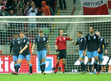 England players stand dejected after Poland's Kamil Glik (not in picture) scores his side's first goal of the game.