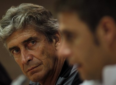 Malaga's coach Manuel Pellegrini, listens to Joaquin Sanchez at the Rosaleda stadium yesterday.