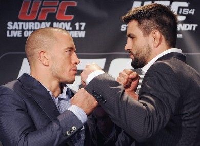 Georges St-Pierre, left, squares off with Carlos Condit.