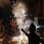 An Indian family lights firecrackers during the Festival of Lights  in New Delhi, India. (AP Photo/Kevin Frayer)