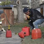 Chris Zaturoski uses a garden hose to attempt to siphon gasoline from his car to use in a generator at his house which is without power in the wake of superstorm Sandy (AP Photo/Mike Groll)