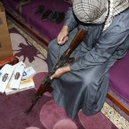 14 February: An Iraqi smuggler dismantles an AK-47 machine-gun at his house in Mosul. To be successfully smuggled into Syria, the rifles are taken apart and hidden in cigarette cartons and kerosene tanks. (AP Photo)