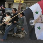 5 February: A pro-Syrian regime protester rides his scooter with his two sons, while holding a Syrian flag bearing a picture of Syrian President Bashar Assad. (AP Photo/Hussein Malla)