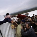 10 December: Syrians who fled their homes struggle to get pillows and blankets distributed at a camp for displaced Syrians, in the village of Atmeh. (AP Photo/Muhammed Muheisen)