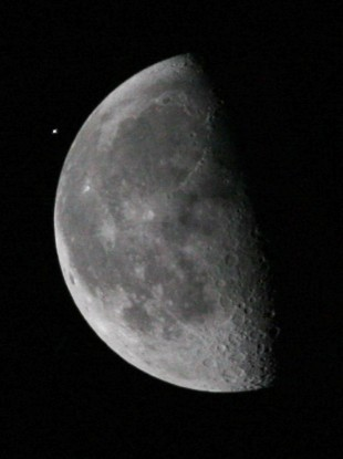 The International Space Station (ISS), upper left, passes the moon as viewed from the Kennedy Space Center, on 5 April, 2010, in Cape Canaveral.